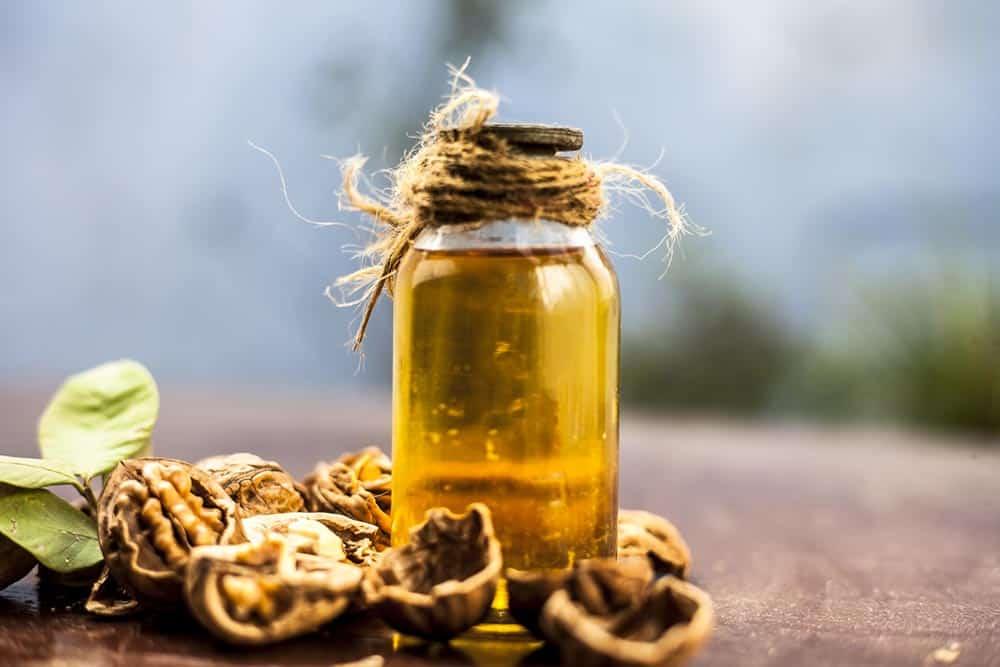 Flacon d'huile de noix avec des noix déposés sur un table en bois